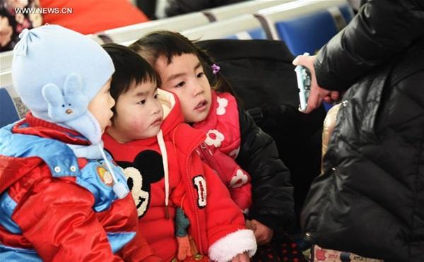 ينتظر أطفال القطار في محطة سكة حديد غرب بكين، 24 يناير