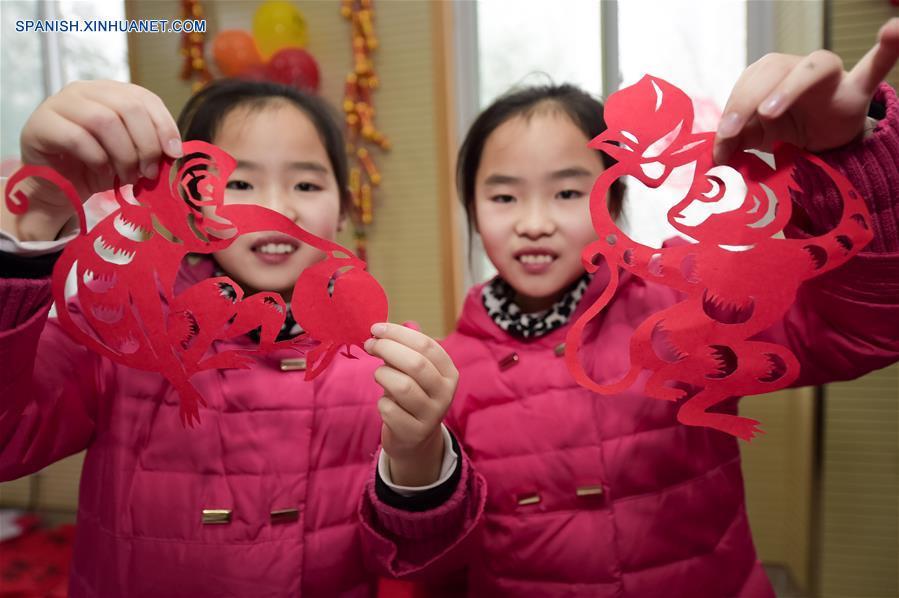 HEFEI, 31 ene (Xinhua) -- Zhu Bingqing (D) y su hermana Zhu Bingjie mostraron cortes de papel de forma de mono en una comunidad de Hefei, en la provincia oriental china de Anhui, el 31 de enero ante la inminente Fiesta de Primavera. (Xinhua/Zhang Duan)