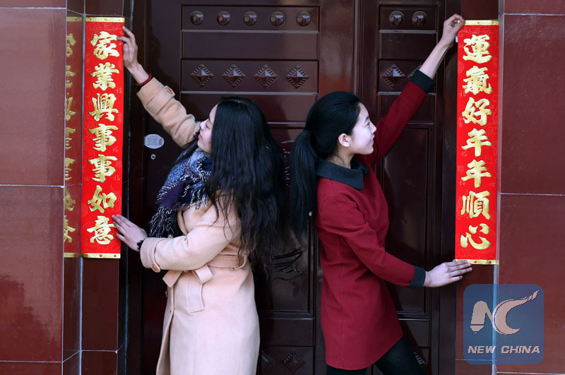 Des jeunes femmes collent des poèmes du printemps sur la porte de maison familiale pour porter chance à la famille le jour du Lichun dans le comté de Wen