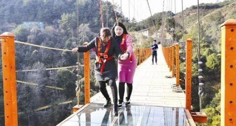 """记者(右)和一名工作人员感受玻璃天桥的""""心跳之旅"""""""
