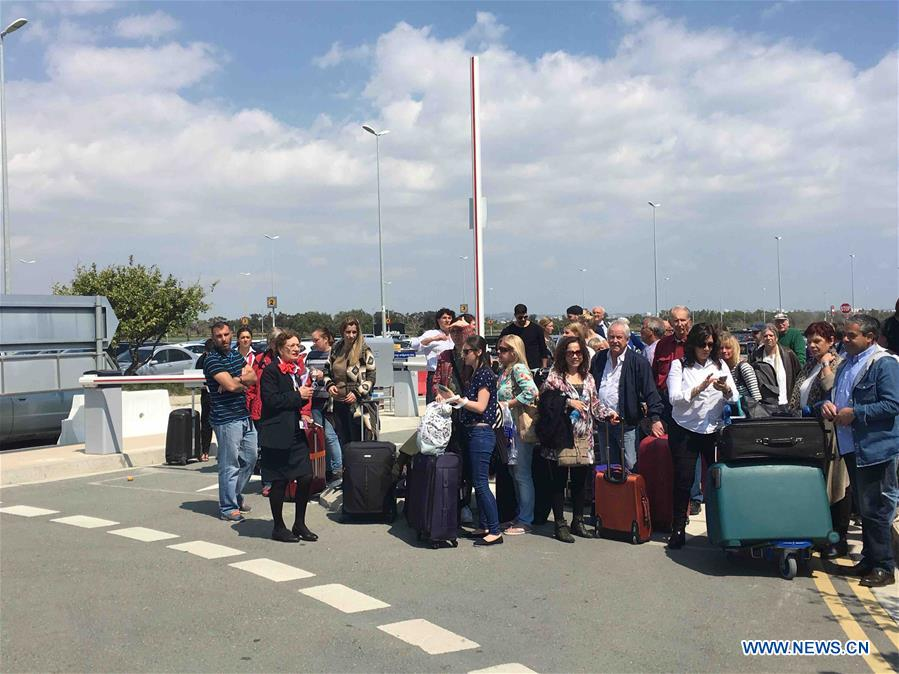 Passengers wait for a bus to Paphos at the Larnaca airport in Larnaca, Cyprus, March 29, 2016. The women and children on a hijacked Egyptian plane have been released after it landed in Larnaca, Cyprus, Cypriot authorities said Tuesday. Larnaca airport has been closed and arriving planes are being redirected to Paphos in western Cyprus. (Xinhua/Zhang Zhang)