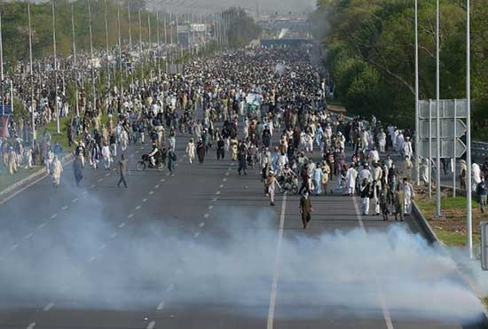 Supporters of executed Islamist Mumtaz Qadri walk through tear gas fired by police during anti-government protest in Islamabad on March 27, 2016.