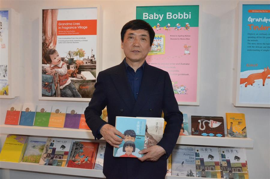 Chinese writer Cao Wenxuan poses with his works at the Bologna Children