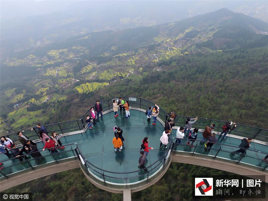 Le 19 mars 2016, des visiteurs admirent les champs de colza depuis la plateforme en verre du site Jianmenguan à Guangyuan dans la province du Sichuan.