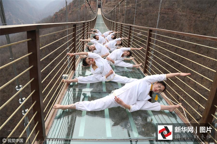 Le 30 mars 2016, une dizaine de jeunes femmes font du yoga sur la passerelle en verre du mont Fuxi à Zhengzhou, dans la province du Henan.