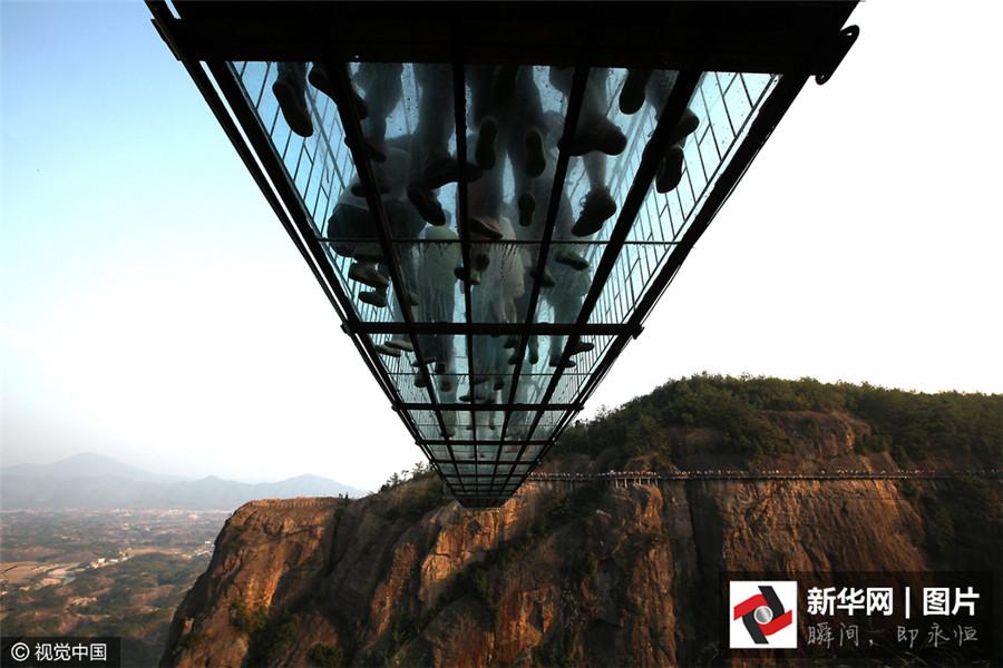 Le 24 octobre 2015, des touristes sur la passerelle en verre du parc géologique Shiniuzhai de Jiangping dans la province du Hunan.