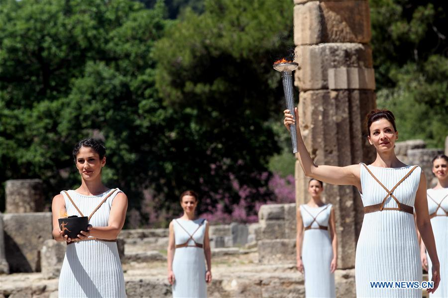Actress Katerina Lehou (R) lights a pot with the Olympic Flame, during the dress rehearsal of the lighting of the Olympic flame at Ancient Olympia, in western Greece on April 20, 2016. (Xinhua/Marios Lolos)