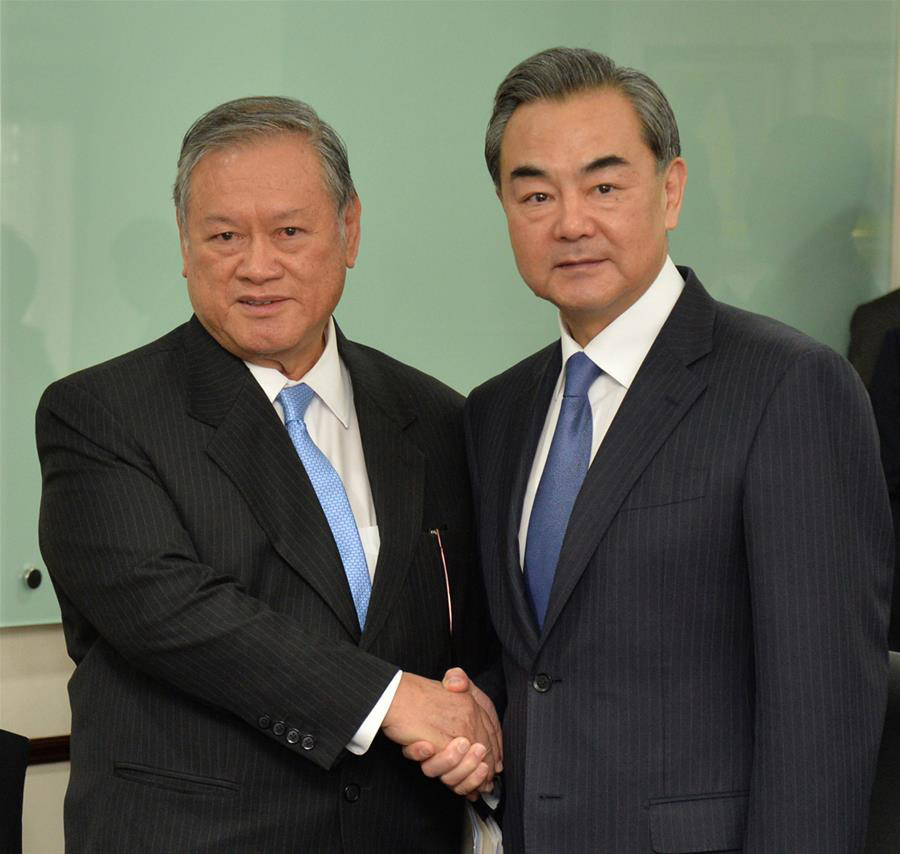 Visiting Chinese Foreign Minister Wang Yi (R) shakes hands with Brunei