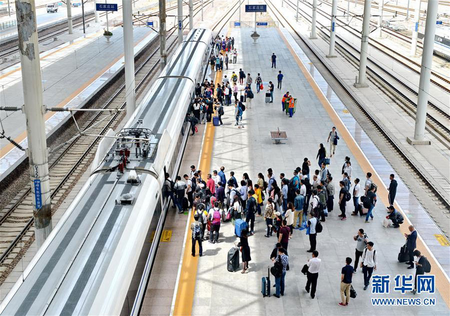 Passengers get on a bullet train at Shijiazhuang Rail Station, north China
