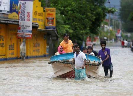 Villagers pull a boat with people after rescuing them, on a flooded road in Biyagama, Sri Lanka May 17, 2016. REUTERS/Dinuka LiyanawatteMore
