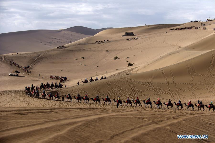 Des touristes visitent le le site de la source du Croissant de lune et des dunes Mingsha, à Dunhuang, dans la province chinoise du Gansu (nord-ouest), le 10 juin 2016. Les Chinois ont joui des vacances de trois jours de la Fête des bateaux-dragons de différentes façons. (Xinhua/Zhang Xiaoliang)