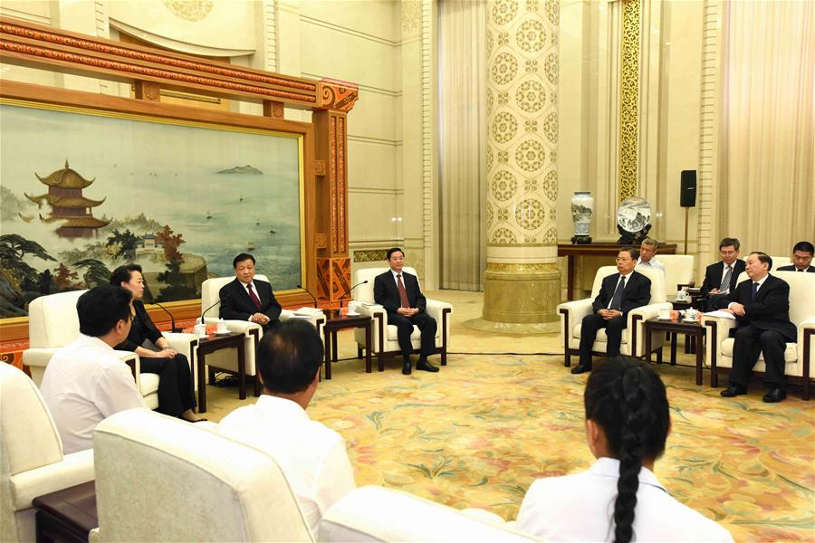 Liu Yunshan (2nd L), a member of the Standing Committee of the Political Bureau of the Communist Party of China (CPC) Central Committee and secretary of the Secretariat of the CPC Central Committee, meets with group members publicizing the deeds of Li Baoguo, a late forestry professor who championed poverty alleviation through afforestation, before a seminar on Li