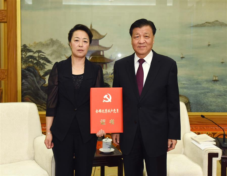 Liu Yunshan (R), a member of the Standing Committee of the Political Bureau of the Communist Party of China (CPC) Central Committee and secretary of the Secretariat of the CPC Central Committee, presents Li Baoguo
