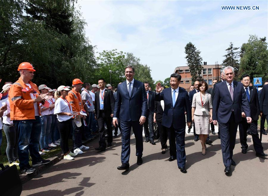 Chinese President Xi Jinping (2nd R, front), accompanied by Serbian President Tomislav Nikolic (1st R, front) and Serbian Prime Minister Aleksandar Vucic (3rd R, front), is welcomed by workers, their families and local citizens as he visits Serbia