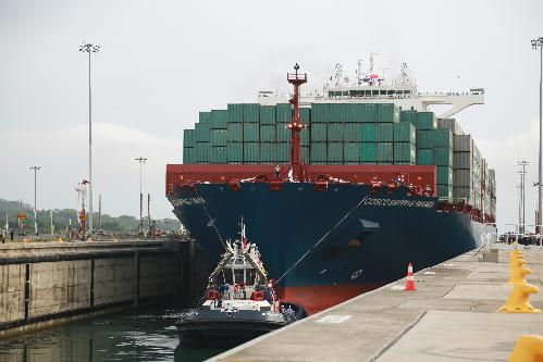 A giant Chinese-chartered freighter nudged its way through the Panama Canal on Sunday to mark the completion of nearly a decade of expansion work expected to boost global trade.