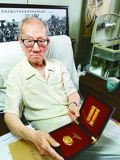 武耀芝老先生和他珍藏的抗战胜利七十周年纪念章。光明日报记者 陈鹏摄