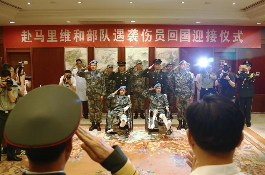 Chinese peacekeepers, who were injured in a terrorist attack in Mali last month, are greeted after returning to Beijing, capital of China, June 27, 2016. Four injured Chinese peacekeepers, with two in serious conditions, returned to Beijing on Monday. Chinese UN peacekeeping soldier Shen Liangliang, 29, was killed in the terrorist attack on the night of May 31 in the northern Malian town of Gao, when a vehicle-borne improvised explosive device was detonated at a United Nations camp. (Xinhua/Zhang Lupeng)