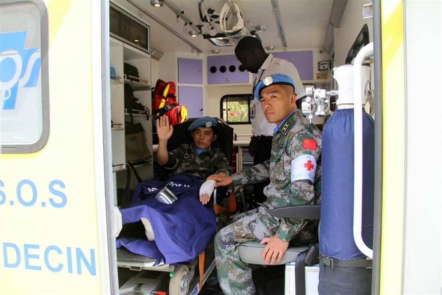 Injured Chinese peacekeeper Si Chongchang (L) waves to people as he leaves a hospital in Dakar, Senegal, on June 26, 2016. Four Chinese peacekeepers, injured in terrorist attacks in Mali, left for China on Sunday. (Xinhua/Wang Meng)