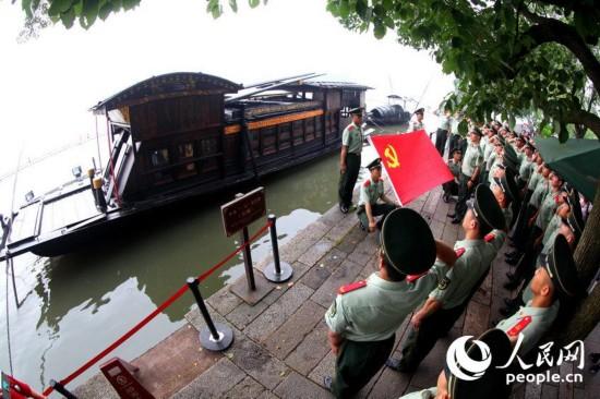 6月23日上午,武警嘉兴市支队组织35名新党员来到党的摇篮——嘉兴南湖红船边,面对党旗庄严宣誓,光荣地加入中国共产党。王健 摄