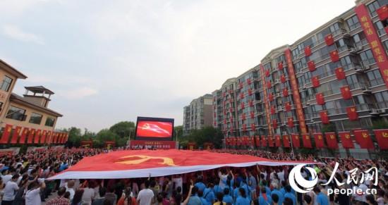 6月25日,山西运城市5000余名业主手持党旗,欢聚在小区感恩广场,庆祝中国共产党建党95周年。图为巨幅党旗传递活动。