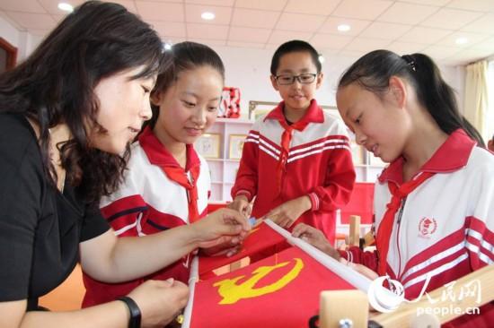 6月28日,呼和浩特市赛罕区西把栅中心校乡村少年宫刺绣班老师指导学生绣党旗,庆祝中国共产党成立95周年。巴特尔 摄