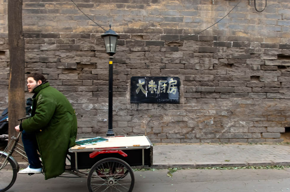 Wheeling his souped-up tricycle that serves as a mobile snack stand, Jamie sets off for business from his residence near Shichahai, a historic scenic area in Beijing, capital of China, Dec. 7, 2011. (Xinhua/Liu Jinhai)