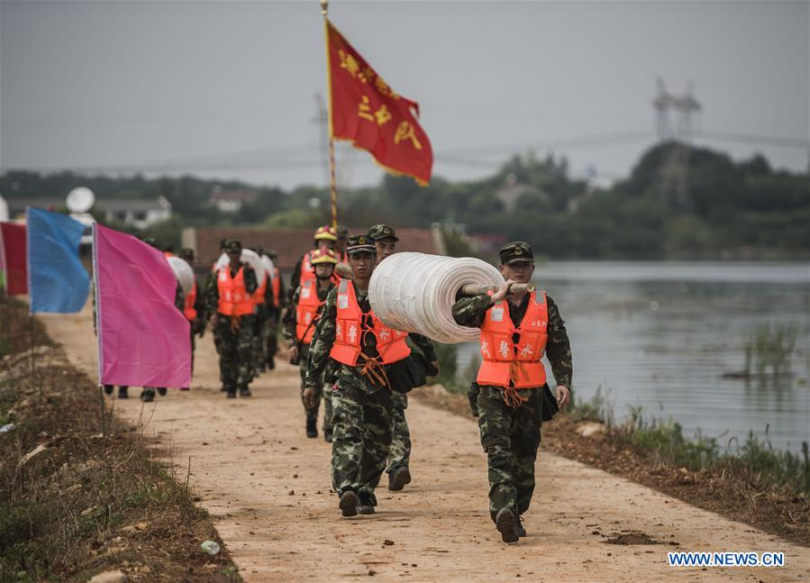 WUHAN, July 13, 2016 (Xinhua) -- Armed police soldiers prepare for the breach of the embankment on the dike of Niushan Lake in central China