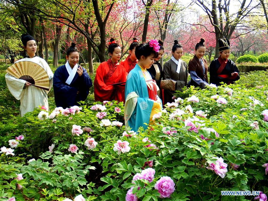 LUOYANG, April 2, 2016 (Xinhua) -- Actors view peony flowers during the Peony Cultural Festival in Luoyang, central China