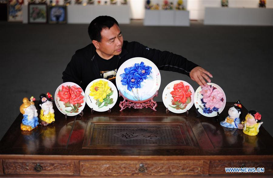 LUOYANG, April 29, 2016 (Xinhua) -- Li Xuewu, a craftsman, shows his porcelain peony handicrafts at Luoyang Peony Porcelain Museum in Luoyang, central China