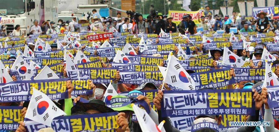 People from Seongju county hold the national flags of South Korea and banners to protest against the deployment of the Terminal High Altitude Area Defense (THAAD), during a rally in Seoul, capital of South Korea, on July 21, 2016. More than 2,000 people from Seongju county, where one THAAD battery will be deployed, gathered at a square in Seoul for a rally on Thursday, to protest against the deployment of THAAD. (Xinhua/Yao Qilin)
