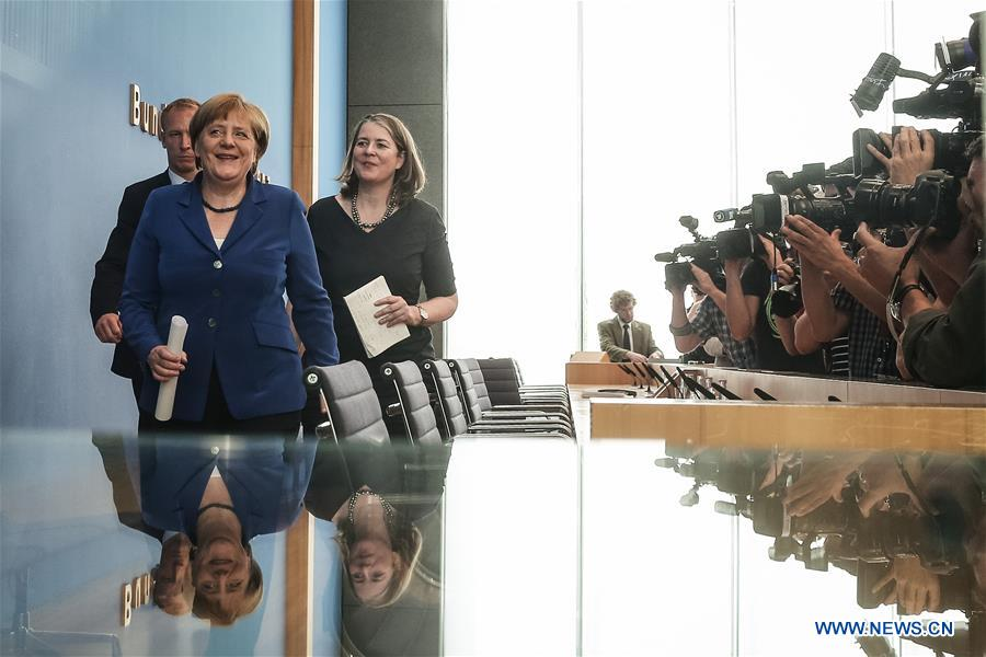 """German Chancellor Angela Merkel (L, front) leaves after a press conference in Berlin, Germany, on July 28. 2016. German Chancellor Angela Merkel repeated her immigration mantra """"We can do it"""" on Thursday after recent string of attacks shocked the country, while raising a nine-point plan to ensure security, which includes increasing security personnel, establishing an information center, and enhancing international cooperation. (Xinhua/Zhang Fan)"""