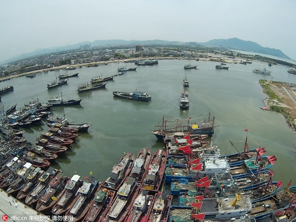 More than 300 fishing vessels flying red flags leave the port at noon for nearby South China Sea fishing ground.