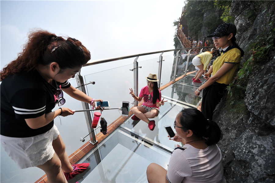 """Tourists pose for photos on the 100-meter-long and 1.6-meter-wide glass bridge built on the cliff of the Tianmen mountains in Zhangjiajie scenic area, Hunan province, on August 1, 2016, as the third glass bridge in the scenic spot opens to the public on Monday. Walking on the high-altitude glass bridge, people can enjoy the dizzying view of the """"heaven-linking Avenue"""", the twisting mountain road from the foot of the mountains to the Tianmen Cave. [Photo/VCG]"""