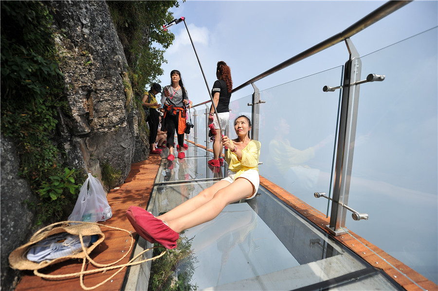 A tourist takes selfie on the 100-meter-long and 1.6-meter-wide glass bridge built on the cliff of the Tianmen mountains in Zhangjiajie scenic area, Hunan province, on August 1, 2016, as the third glass bridge in the Tianmen scenic spot opens to the public. [Photo/VCG]