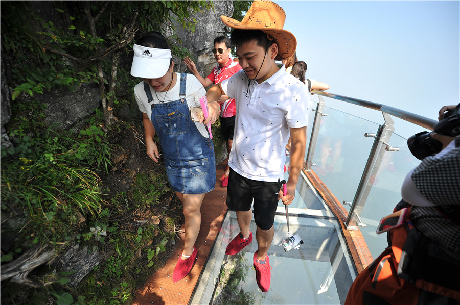 Visitors walk on the narrow glass bridge built on the cliff of the Tianmen mountains in Zhangjiajie scenic area, Hunan province, on August 1, 2016, as the third glass bridge in the Tianmen scenic spot opens to the public. [Photo/VCG]