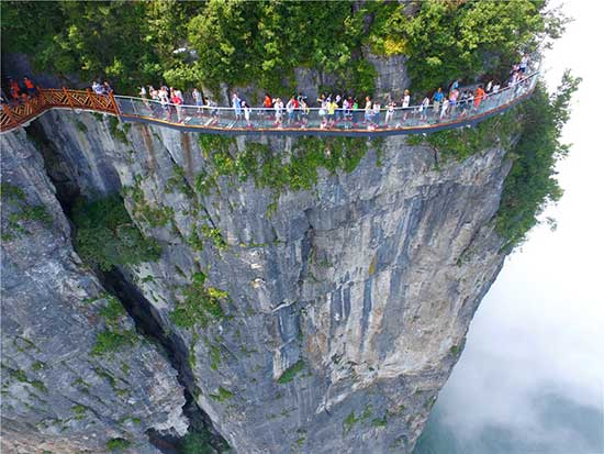 """Tourists walk on the newly opened glass bridge, which offers visitos the amazing view of the """"heaven-linking Avenue"""", the twisting mountain road from the foot of the Tianmen mountains to the Tianmen Cave, in Zhangjiajie scenic area in Hunan province on August 1, 2016. [Photo/VCG]"""