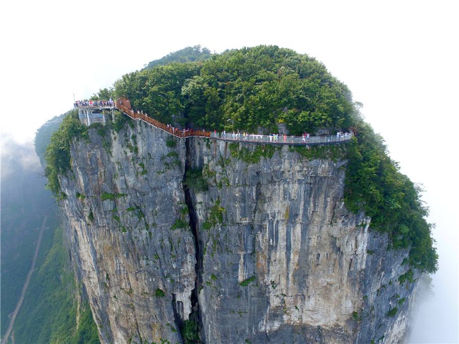 """Tourists walk on the newly opened glass bridge, which offers visitos the dizzying view of the """"heaven-linking Avenue"""", the twisting mountain road from the foot of the Tianmen mountains to the Tianmen Cave, in Zhangjiajie scenic area in Hunan province on August 1, 2016. [Photo/VCG]"""