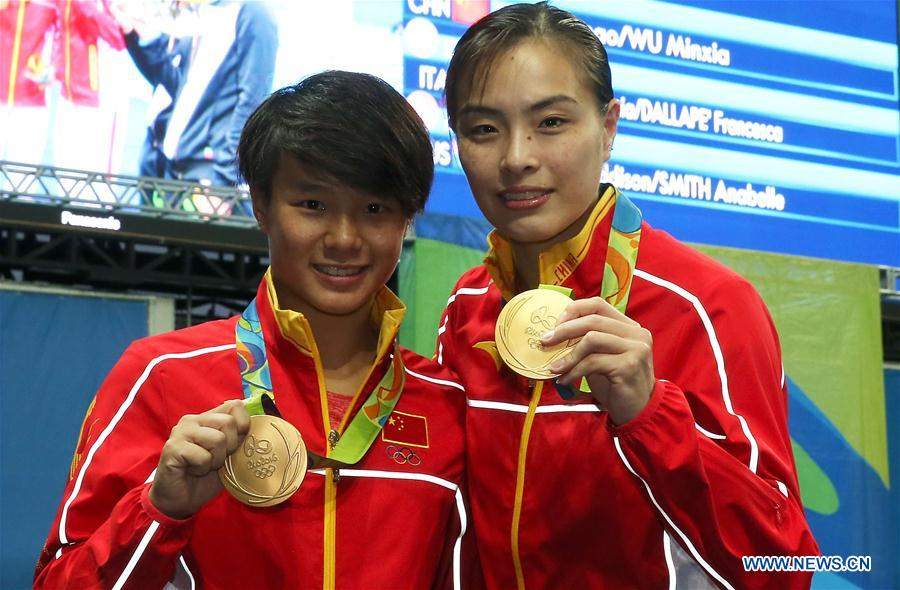 Chinese diving athletes Wu Minxia (R) and Shi Tingmao show gold medals at the awarding ceremony of women