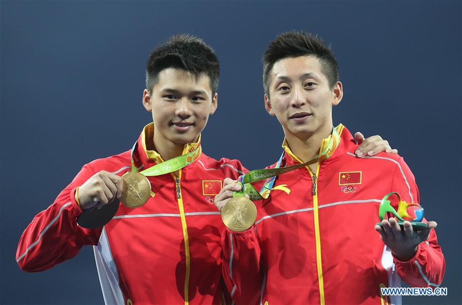 Lin Yue (R) and Chen Aisen of China show gold medals at the awarding ceremony of the men