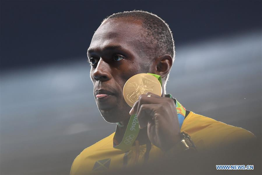 Usain Bolt of Jamaica shows the gold medal at the awarding ceremony of men