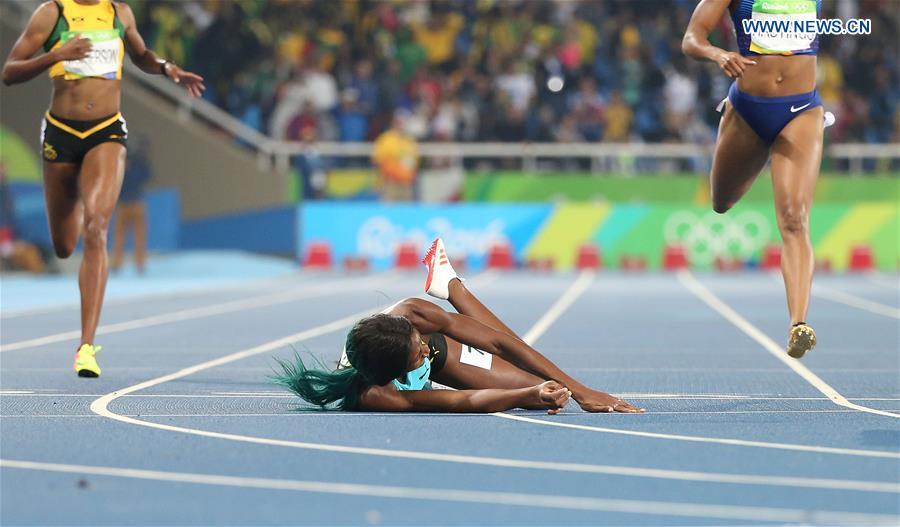 Shaunae Miller of Bahamas (C) falls during the women
