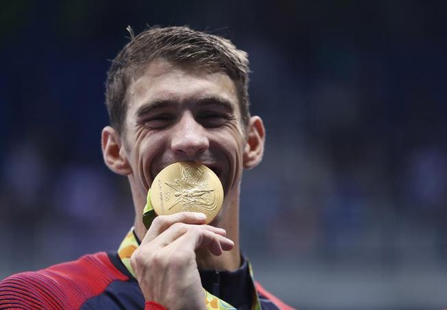 8月13日,美国队队员菲尔普斯在颁奖典礼后展现金牌