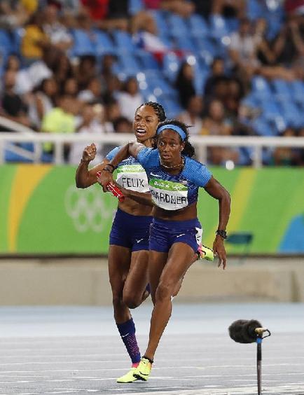 8月18日,美国队选手费利克斯(左)在比赛优游品牌国际与队友加德纳交代棒