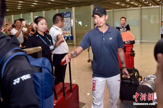 图为林丹走出机场,受到好友鲍春来的热情迎接