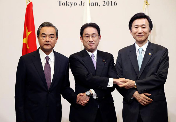 Japanese Foreign Minister Fumio Kishida (C), Chinese Foreign Minister Wang Yi (L) and South Korean Foreign Minister Yun Byung-Se pose for the photographers prior to the official banquet of the trilateral foreign minister