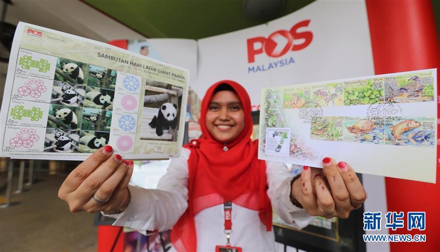 """一名邮政局职员展示以""""熊猫宝宝""""为主题的邮票(左)"""