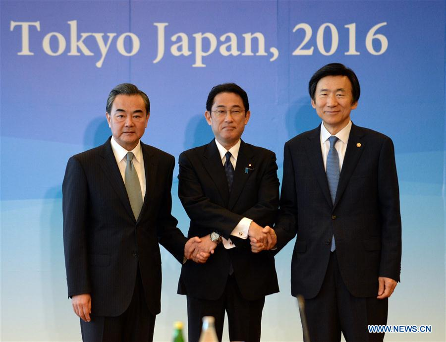 Chinese Foreign Minister Wang Yi, Japanese Foreign Minister Fumio Kishida and South Korean Foreign Minister Yun Byung Se (from L to R) shake hands as they attend the 8th trilateral foreign ministers