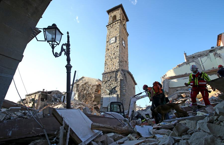 Rescuers walk past the bell tower with the clock showing the time of the earthquake in Amatrice, central Italy, August 24, 2016. [Photo/Agencies]