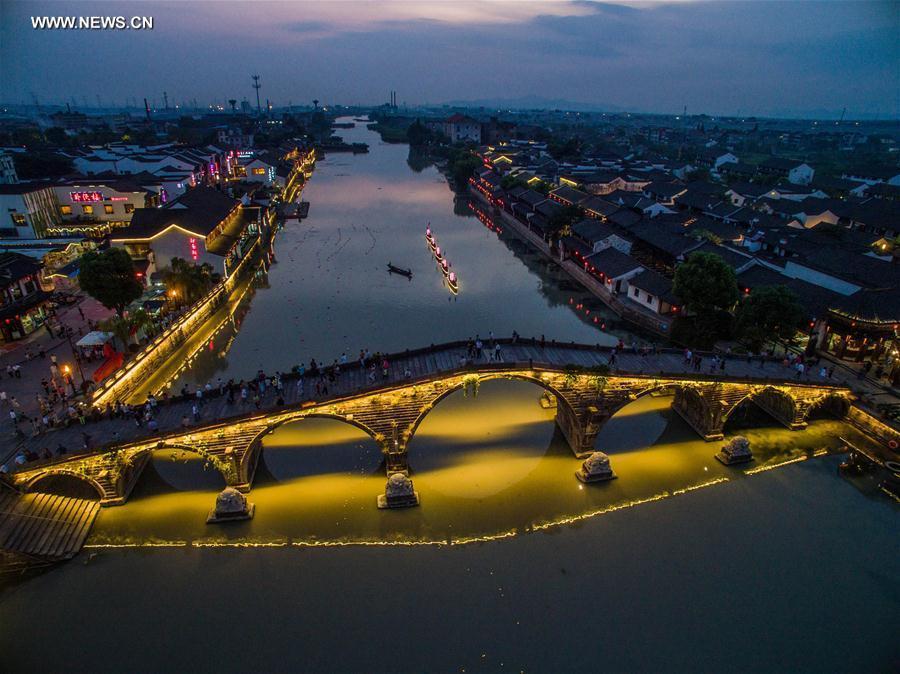 Tourists walk on the ancient Guangji Bridge in Tangqi Town, Hangzhou City, capital of east China