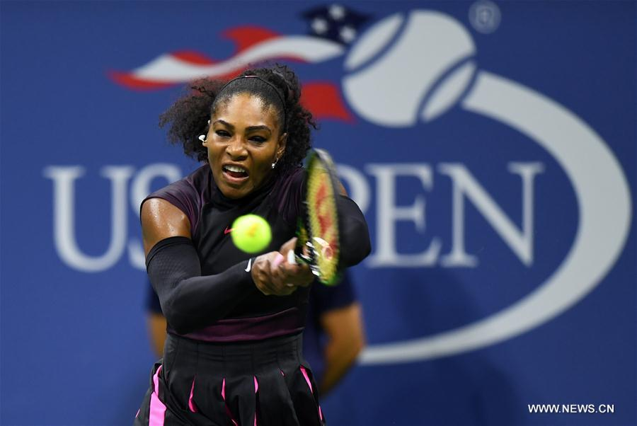 Serena Williams of the United States returns a ball to Simona Halep of Romania during the women